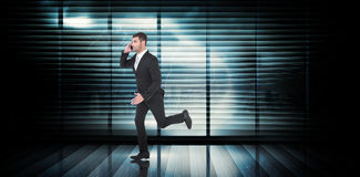Composite image of businessman running on the phone Stock Photos