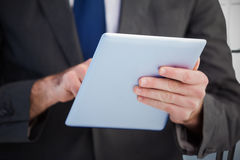 Composite image of businessman scrolling on his digital tablet Stock Images