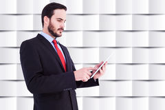Composite image of businessman scrolling on his digital tablet Royalty Free Stock Photos