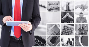 Composite image of businessman scrolling on his digital tablet Stock Image
