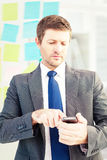Composite image of businessman sending a text message Royalty Free Stock Photos
