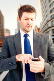 Composite image of businessman sending a text message Royalty Free Stock Image