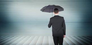 Composite image of businessman sheltering under black umbrella Stock Photos