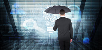 Composite image of businessman sheltering under black umbrella. Businessman sheltering under black umbrella against room with large window looking on city Royalty Free Stock Photos