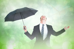 Composite image of businessman sheltering under black umbrella testing Stock Photos