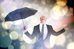 Composite image of businessman sheltering under black umbrella testing Stock Photography