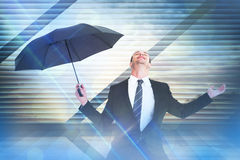 Composite image of businessman sheltering under black umbrella testing Royalty Free Stock Photo