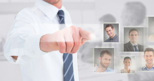 Composite image of businessman in shirt presenting at camera Stock Photos