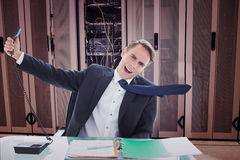 Composite image of businessman shouting as he holds out phone. Businessman shouting as he holds out phone against data center Royalty Free Stock Images