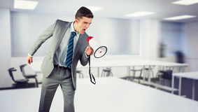 Composite image of businessman shouting through megaphone Stock Photos