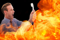 Composite image of businessman shouting at phone Royalty Free Stock Image