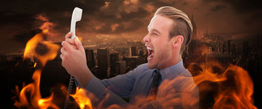 Composite image of businessman shouting at phone. Businessman shouting at phone against stormy sky over city Stock Photos