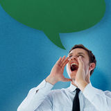 Composite image of businessman shouting with speech bubble. Businessman shouting with speech bubble against blue background with vignette Royalty Free Stock Image