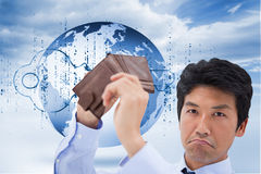 Composite image of businessman showing his empty wallet. Businessman showing his empty wallet against digital blue key with matrix and a planet Stock Photo