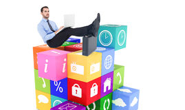 Composite image of businessman sitting on the floor with feet up on suitcase Stock Image
