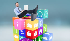 Composite image of businessman sitting on the floor with feet up on suitcase Royalty Free Stock Photography