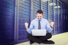 Composite image of businessman sitting with his laptop cheering. Businessman sitting with his laptop cheering against server room Royalty Free Stock Photos