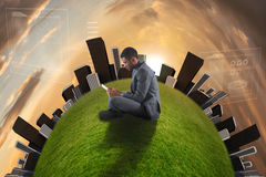 Composite image of businessman sitting and holding tablet Stock Photo