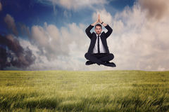 Composite image of businessman sitting in lotus pose with hands together Stock Photo