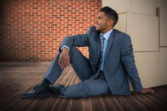 Composite image of businessman sitting near cardboard boxes against white background stock photo