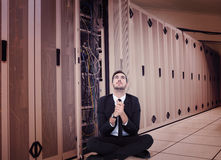 Composite image of businessman sitting praying and looking up Royalty Free Stock Photography