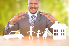Composite image of businessman smiling behind car, family and house illustration. Businessman smiling behind car, family and house illustration against detail Stock Photography