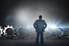 Composite image of businessman standing back to the camera with hands on hip Stock Photos