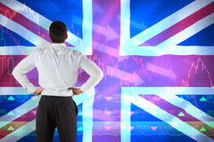 Composite image of businessman standing back to the camera with hands on hips stock photo