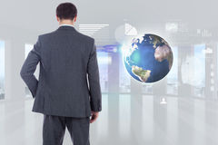 Composite image of businessman standing with hand on hip Royalty Free Stock Images