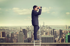 Composite image of businessman standing on ladder Royalty Free Stock Photo