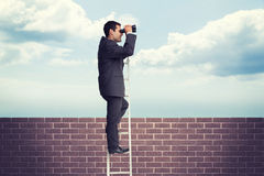 Composite image of businessman standing on ladder Stock Photography
