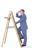 Composite image of businessman standing on ladder looking Stock Image