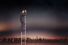 Composite image of businessman standing on ladder using binoculars Stock Images