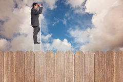 Composite image of businessman standing on ladder using binoculars Royalty Free Stock Photo