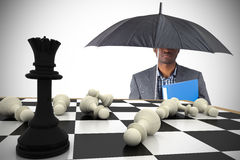 Composite image of businessman standing under umbrella Royalty Free Stock Image