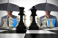 Composite image of businessman standing under umbrella with chessboard Royalty Free Stock Photos