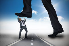 Composite image of businessman stepping on tiny businessman Stock Photo