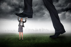 Composite image of businessman stepping on tiny businesswoman Stock Photo