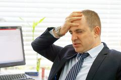 Composite image of businessman stressed out at work. Close-up of an office worker in stress in front of a computer. Businessman in shock at his workplace in the Stock Photography