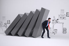 Composite image of businessman in suit carrying something heavy Stock Images