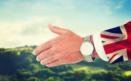 Composite image of businessman in suit clenching fists. Businessman in suit clenching fists against digitally generated great britain national flag Royalty Free Stock Photos