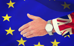 Composite image of businessman in suit clenching fists. Businessman in suit clenching fists against digitally generated great britain national flag Stock Images