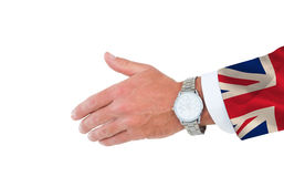 Composite image of businessman in suit clenching fists. Businessman in suit clenching fists against digitally generated great britain national flag Royalty Free Stock Images
