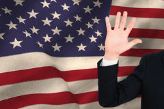 Composite image of businessman in suit with hand raised Stock Photo