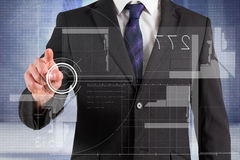 Composite image of businessman in suit pointing finger at interface Royalty Free Stock Photo