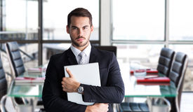 Composite image of businessman in suit posing with his laptop Stock Image