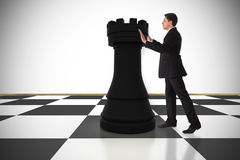 Composite image of businessman in suit pushing chess piece Royalty Free Stock Photos