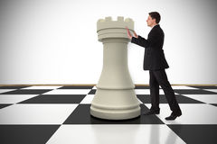 Composite image of businessman in suit pushing chess piece Stock Image