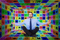 Composite image of businessman in suit sitting in lotus pose Stock Photo