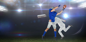 Composite image of businessman tackling a football player Stock Image